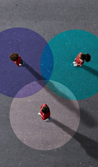 Group of children photographed from above on various painted tarmac surface at sunset